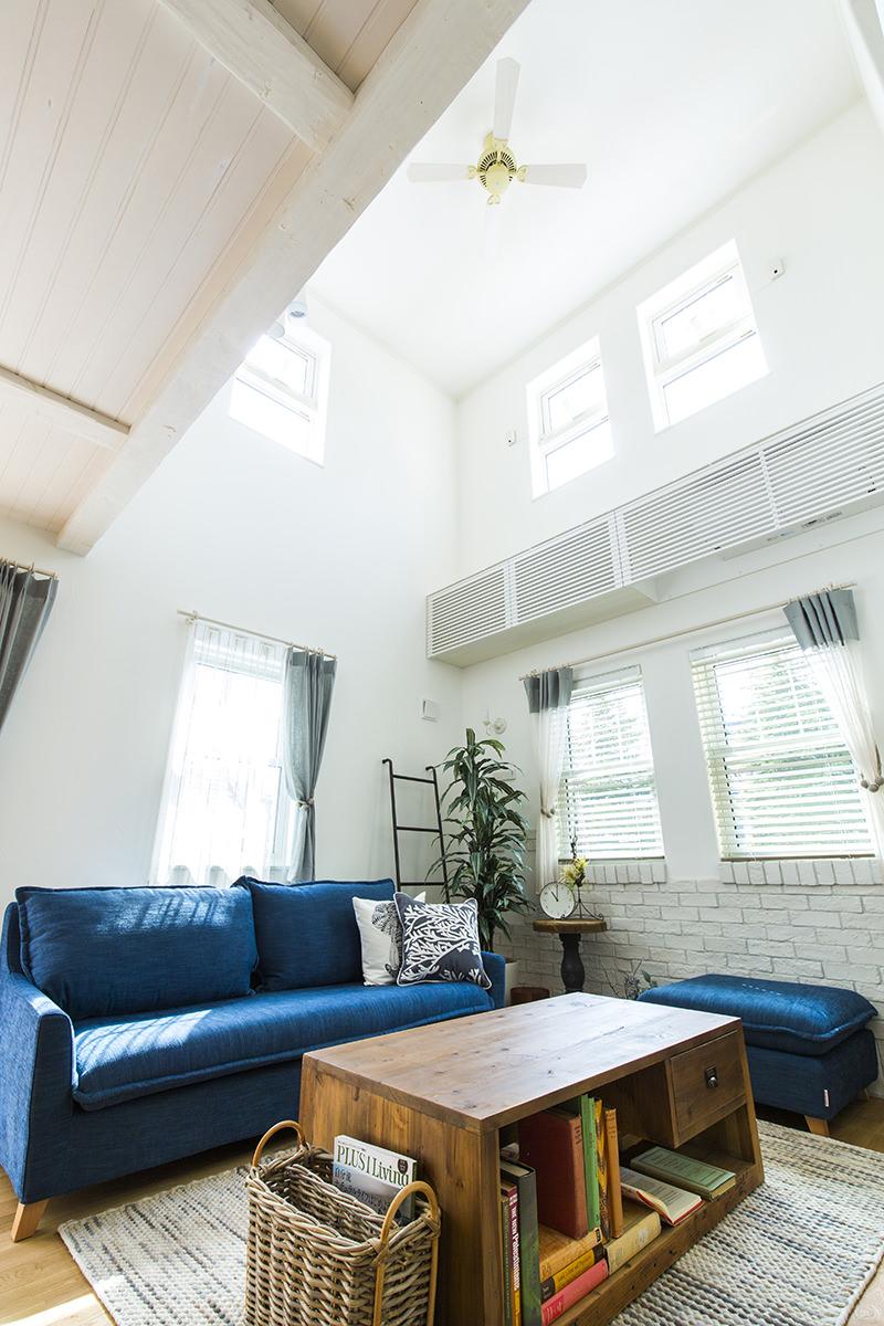ブルーのソファが映える白い塗り壁のリビング
