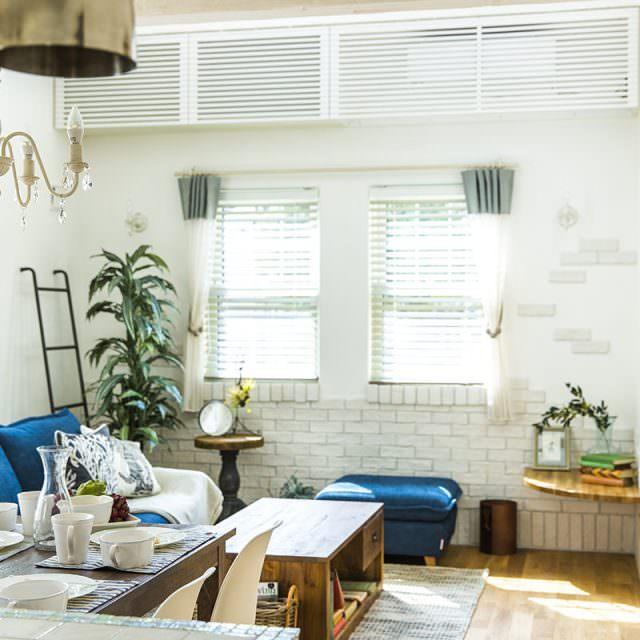 壁にランダムに貼った白レンガとブルーのソファが調和したリビング空間