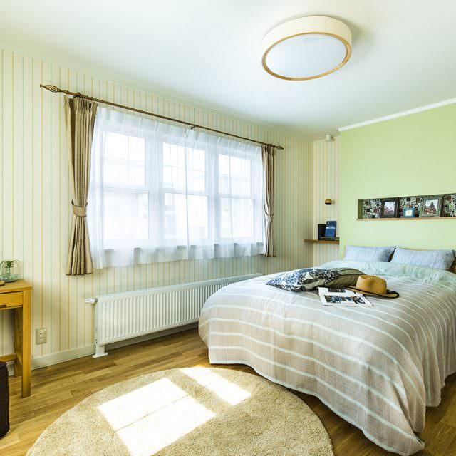 やさしいグリーンの壁紙とゴールドのアイアンカーテンホルダーがおしゃれな主寝室