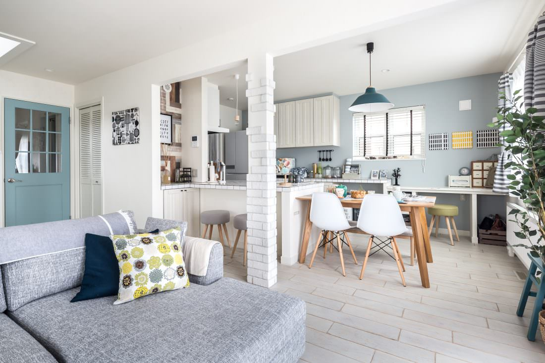 注文住宅事例 ブルグレーの壁紙のダイニングキッチンやファブリックパネルを飾ったリビング