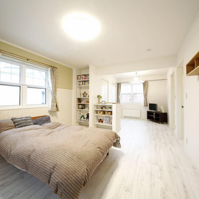 グリーンと木調の壁紙を上下で貼り分けした落ち着いた寝室