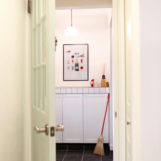 ガラス入りの木製ドアとタイルのシューズボックスがおしゃれな玄関