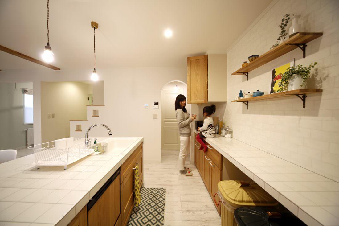 白いタイルと木の扉が合う清潔感あるキッチン