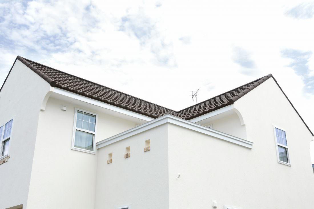 青空に映える白い塗り壁に三角屋根の外観