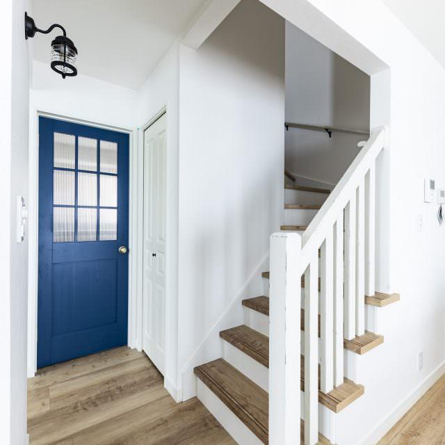 ブルーのドアと階段手すりのアンティーク塗装がおしゃれ