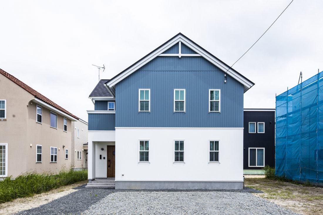 ブルーのサイディングと白い塗り壁のツートーンがおしゃれな北欧デザインの外観