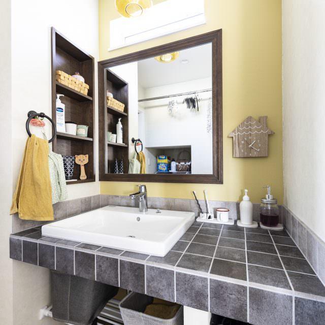 マスタードカラーの壁紙が印象的な洗面台