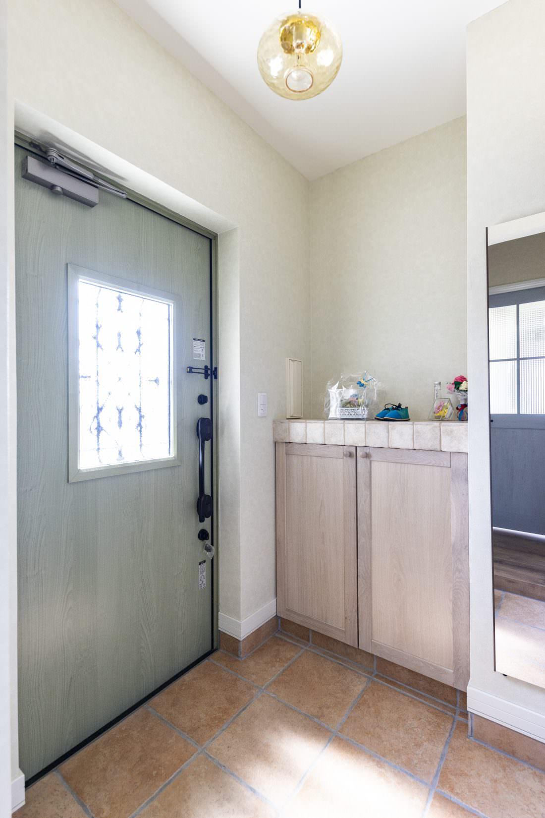 グリーンの玄関ドアがアクセントの玄関