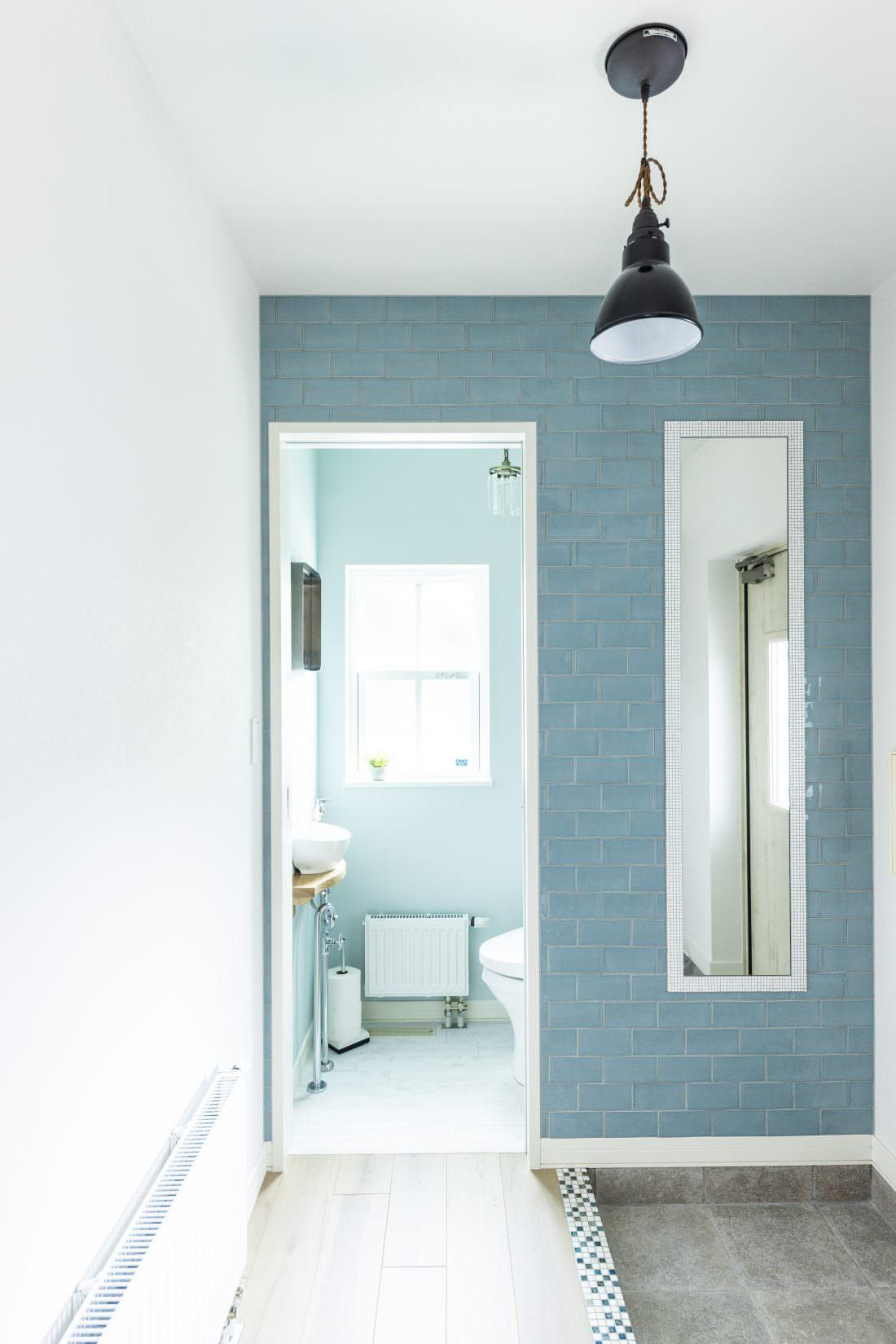 ブルーのタイル張りと姿見が印象的な玄関