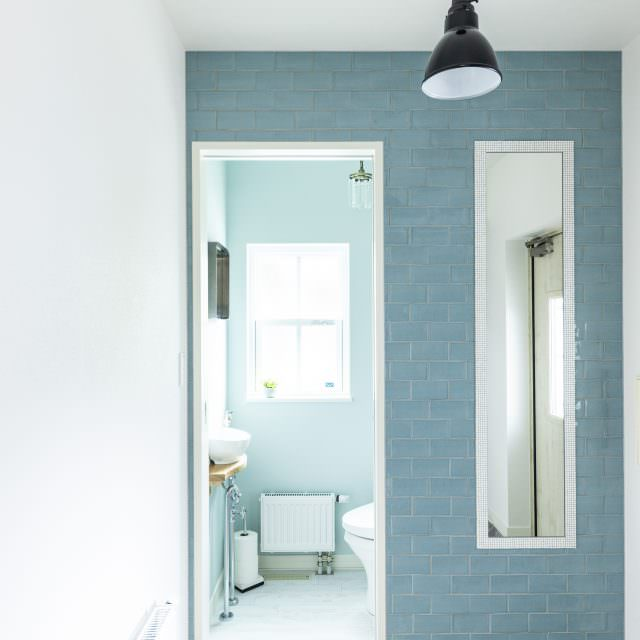 ブルーのタイル張りと姿見が印象的な玄関。