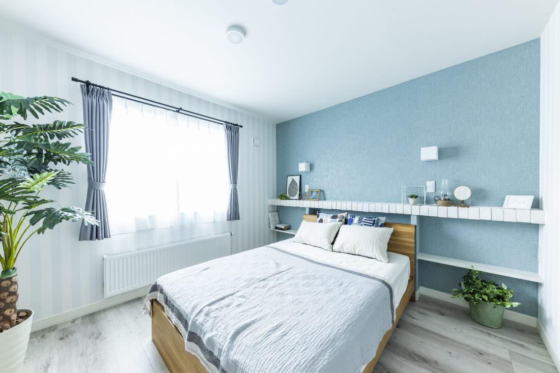 ブルーの壁紙と白ブリックの棚板のコントラストが北欧の雰囲気を演出する寝室
