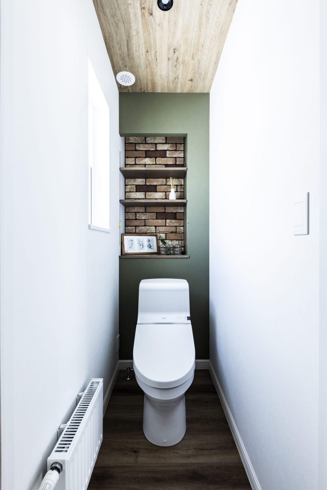 モスグリーンの壁紙でお店のようなおしゃれなトイレ