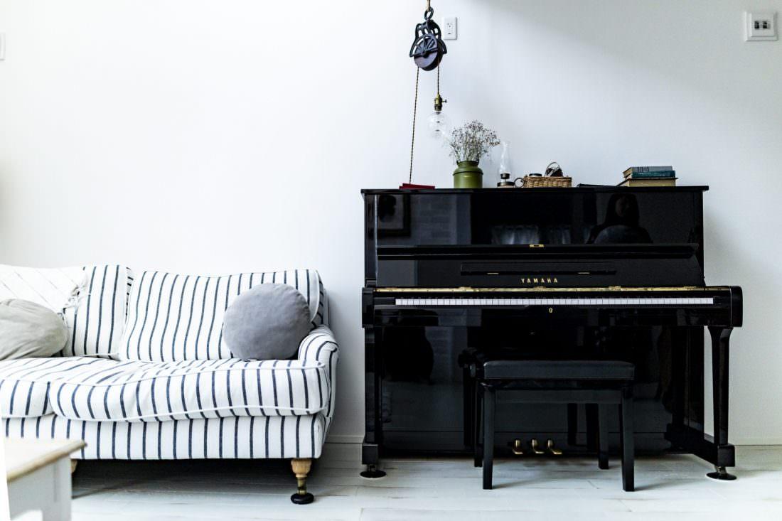 ピアノとボーダー柄のソファがあるフレンチシックな家