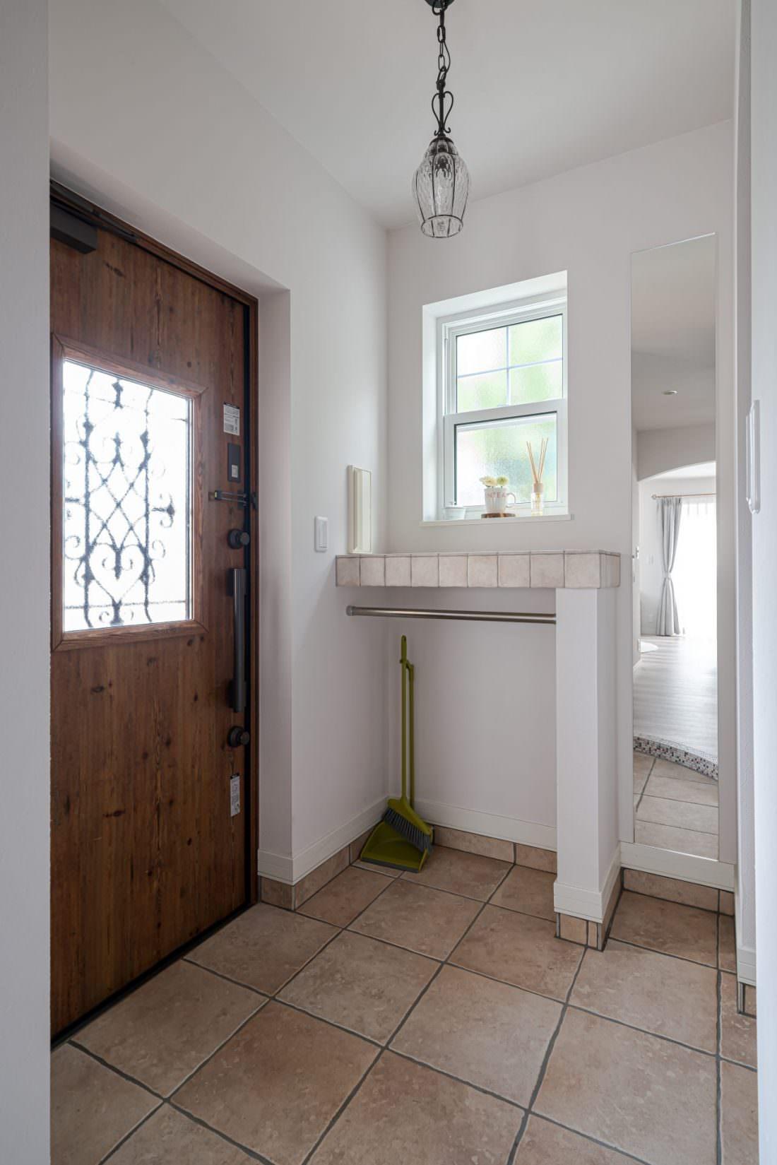 茶色い木目調の玄関ドアにタイルのカウンターのある玄関
