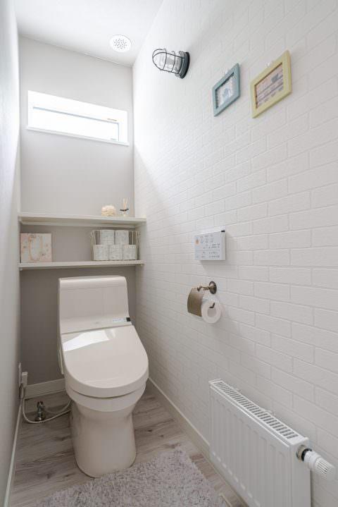 レンガ調のクロスを貼った清潔感のあるトイレ