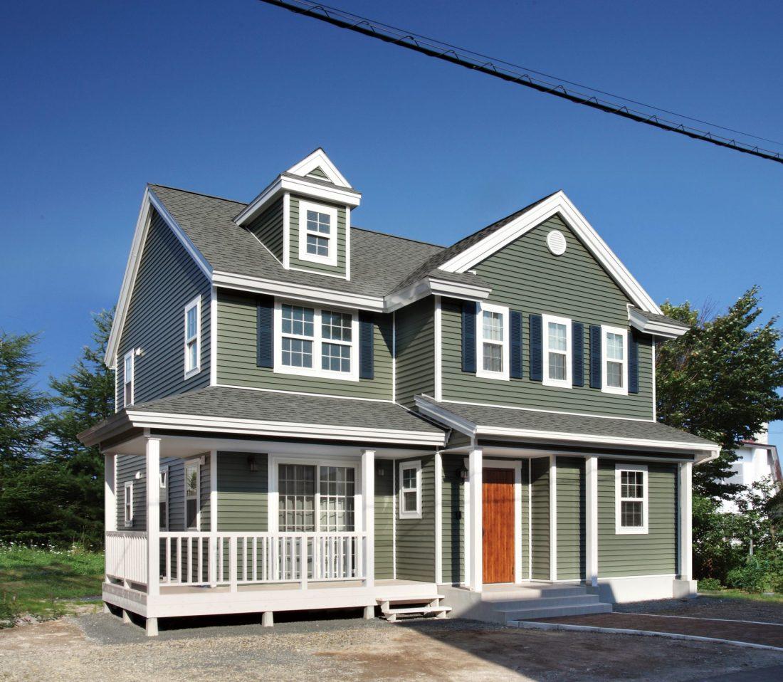 グリーンのサイディングとドーマーがあるアメリカンデザインの家