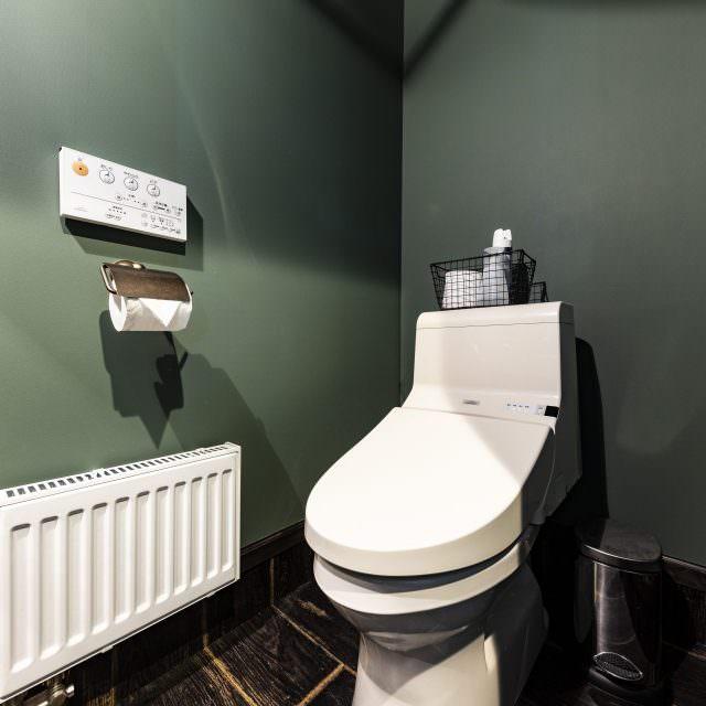 ダークグリーンの壁紙がおしゃれなトイレ