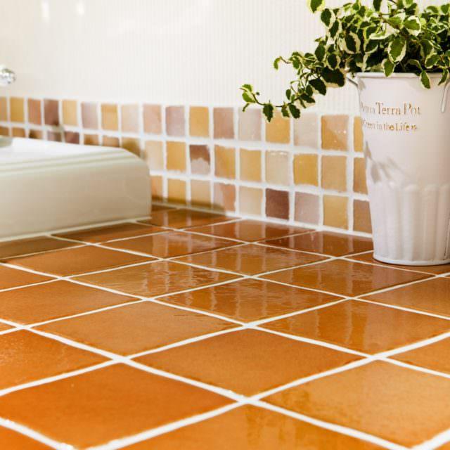 オレンジのタイルが個性的な洗面バニティ