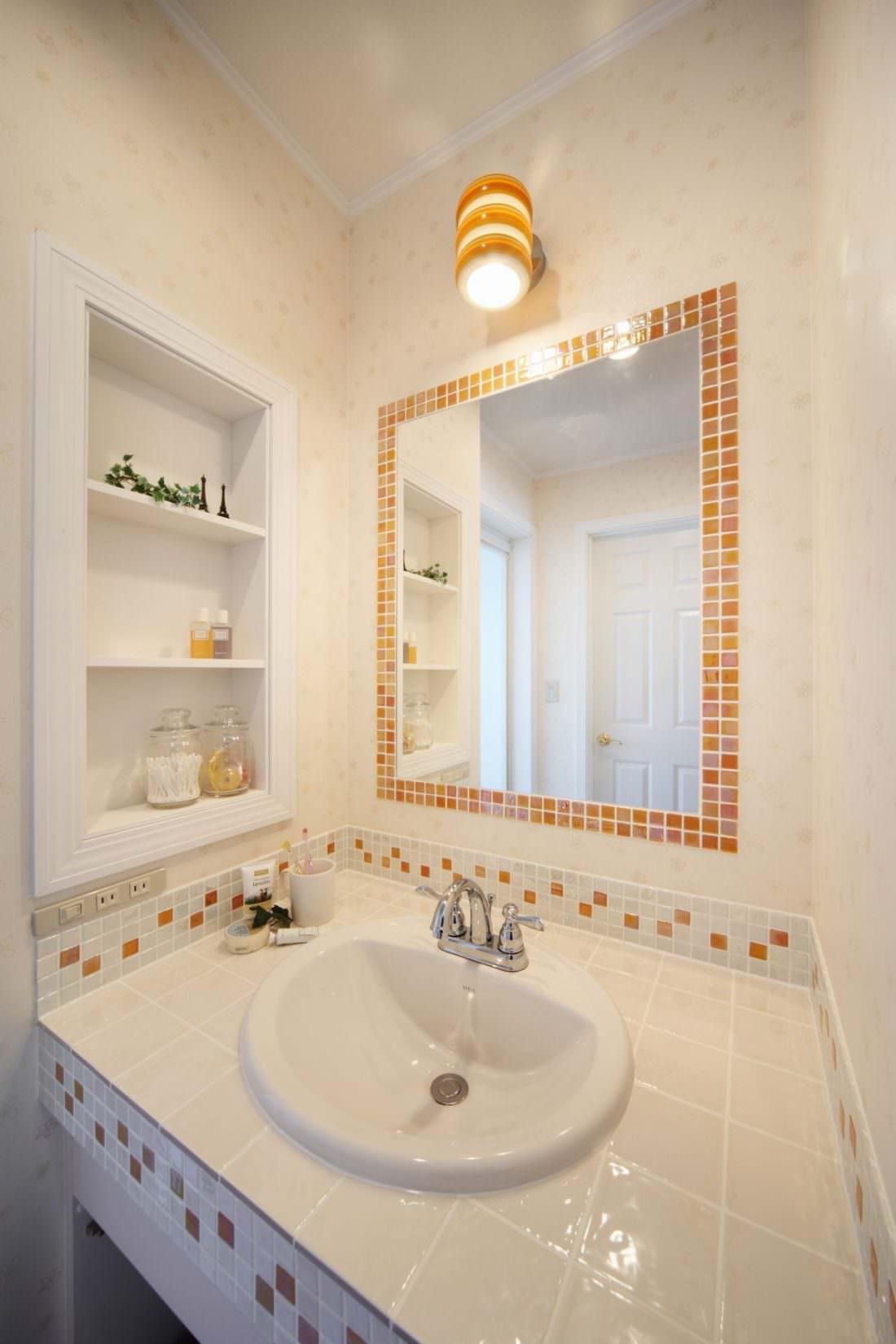 洗面台のミラーにオレンジのモザイクタイルをあしらって
