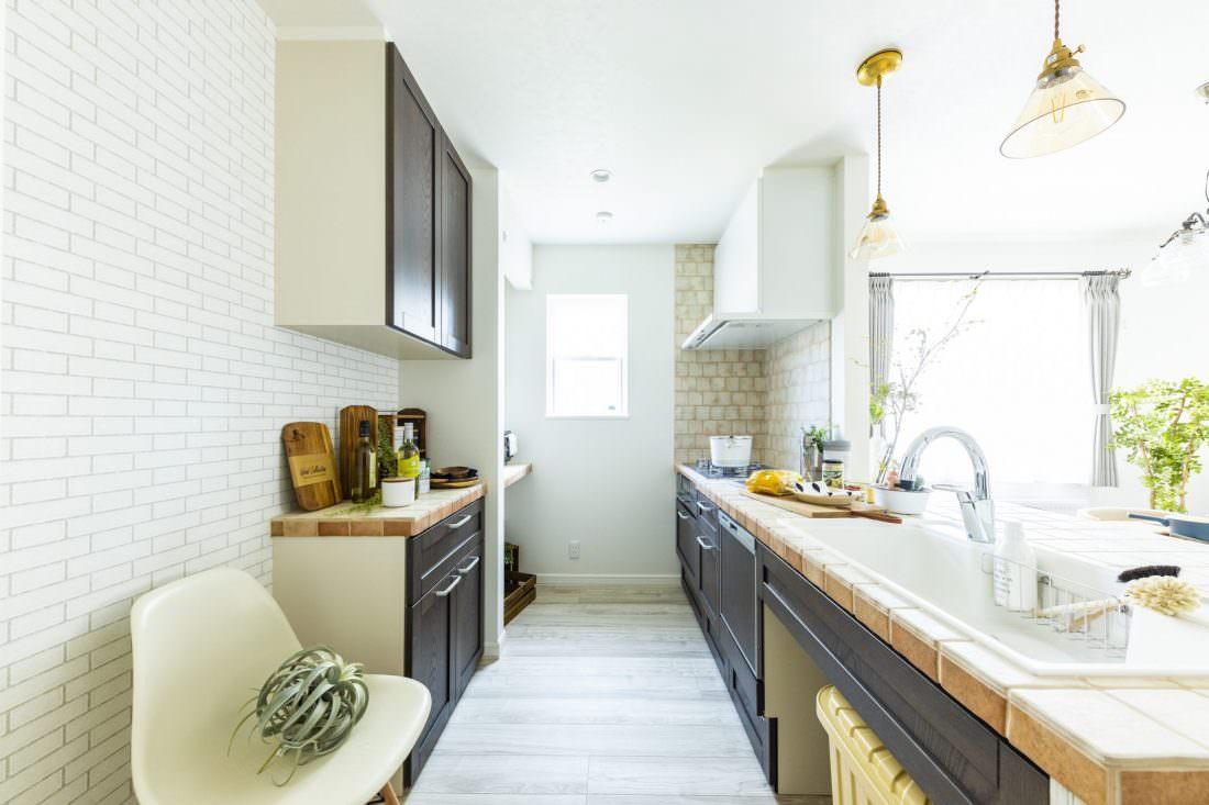 アンティークタイルとダークブラウンの扉がシックなキッチン
