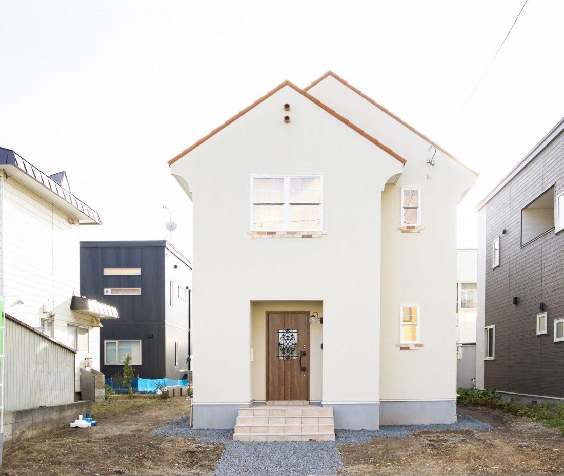 白い塗り壁に赤い三角屋根の輸入住宅