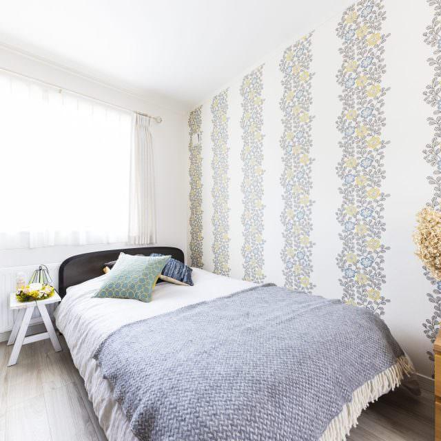 花のパターンが入った印象的なクロスを用いた寝室