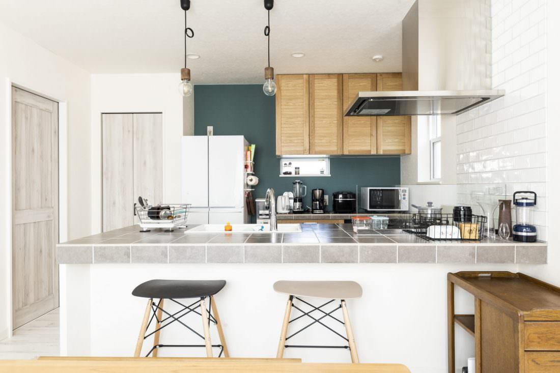 グリーンの壁紙が映えるオシャレなタイルキッチン
