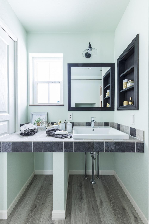 シャーベットカラーがおしゃれなオリジナル洗面台。グレーのタイルや木のニッチや鏡、照明などベストバランス◎