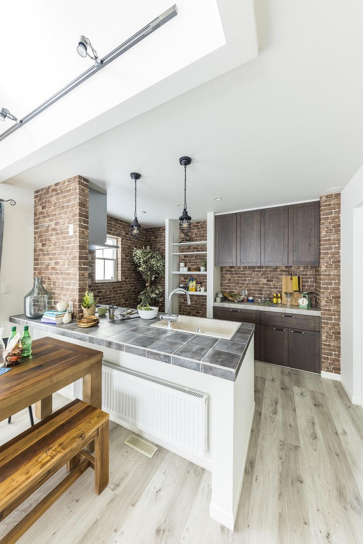 レンガ調クロスがカフェのような雰囲気のキッチン。キッチンタイルの質感が重厚感や上質な印象を与えます。