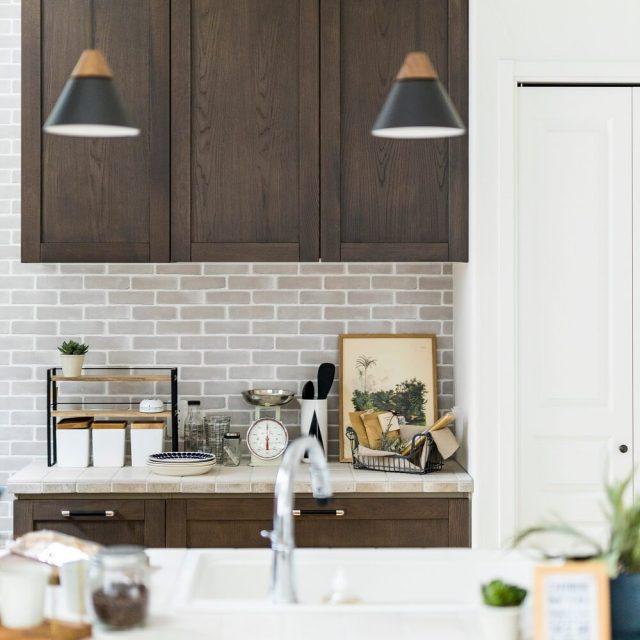 グレーのレンガ調クロスがカフェのような雰囲気のキッチン