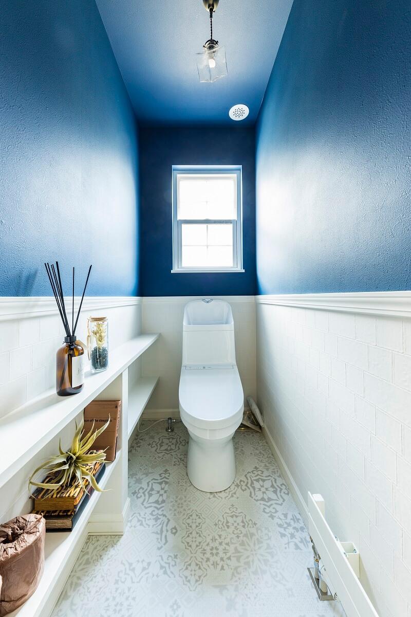 上下で見切りをつけたトイレ。深いブルーの壁紙がキレイ。