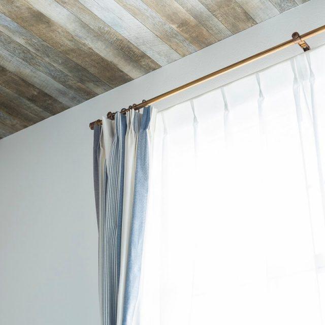 天井に古材風のアクセントクロスを貼った居室。カーテンやカーテンレールも素敵です!